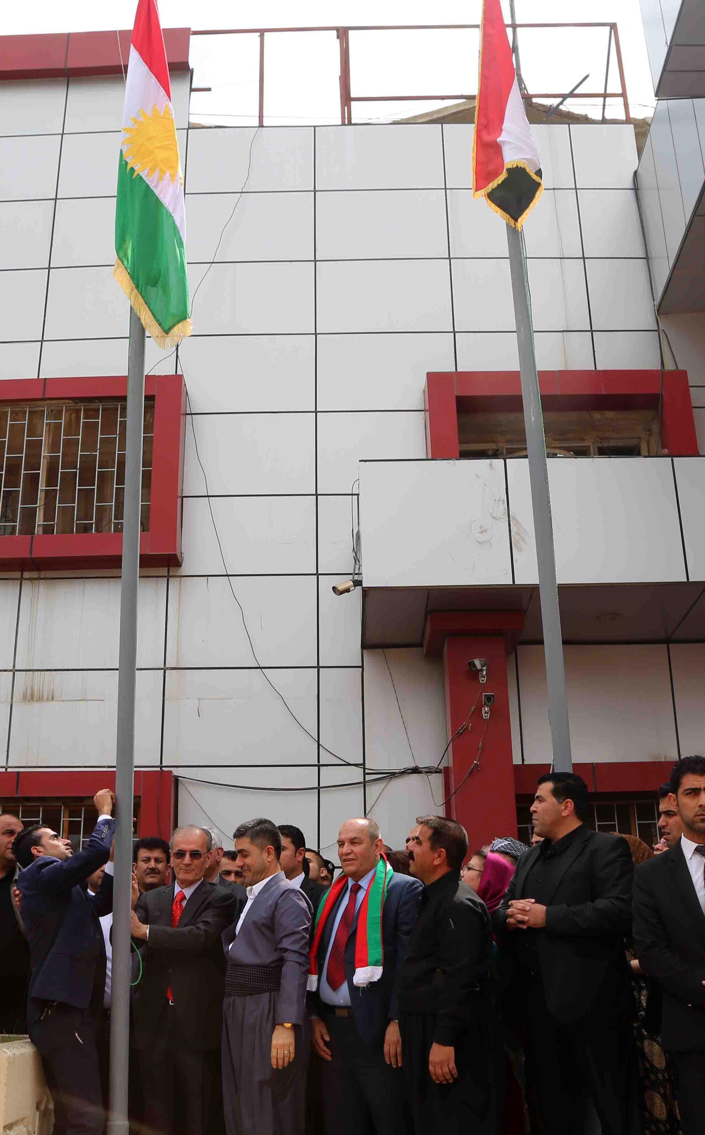 محافظ كركوك نجم الدين كريم يرفع العلم الكردي، إلى جانب العراقي، على مدخل مبنى حكومي في كركوك