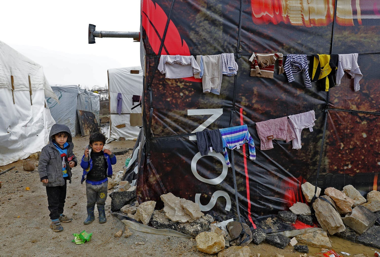 Syrian refugee children walk at an unofficial refugee camp in the village of Deir Zannoun in Lebanon's Bekaa valley on January 31, 2017.