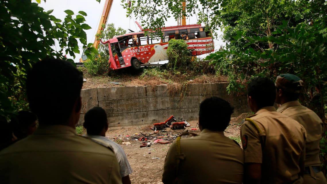 Policemen watch as a bus is pulled out from a ditch after it met with an accident on the outskirts of Mumbai, India, Sunday, June 5, 2016. The speeding bus struck two cars on a highway in a crash early Sunday that killed and injured passengers in western India, police said. (AP)