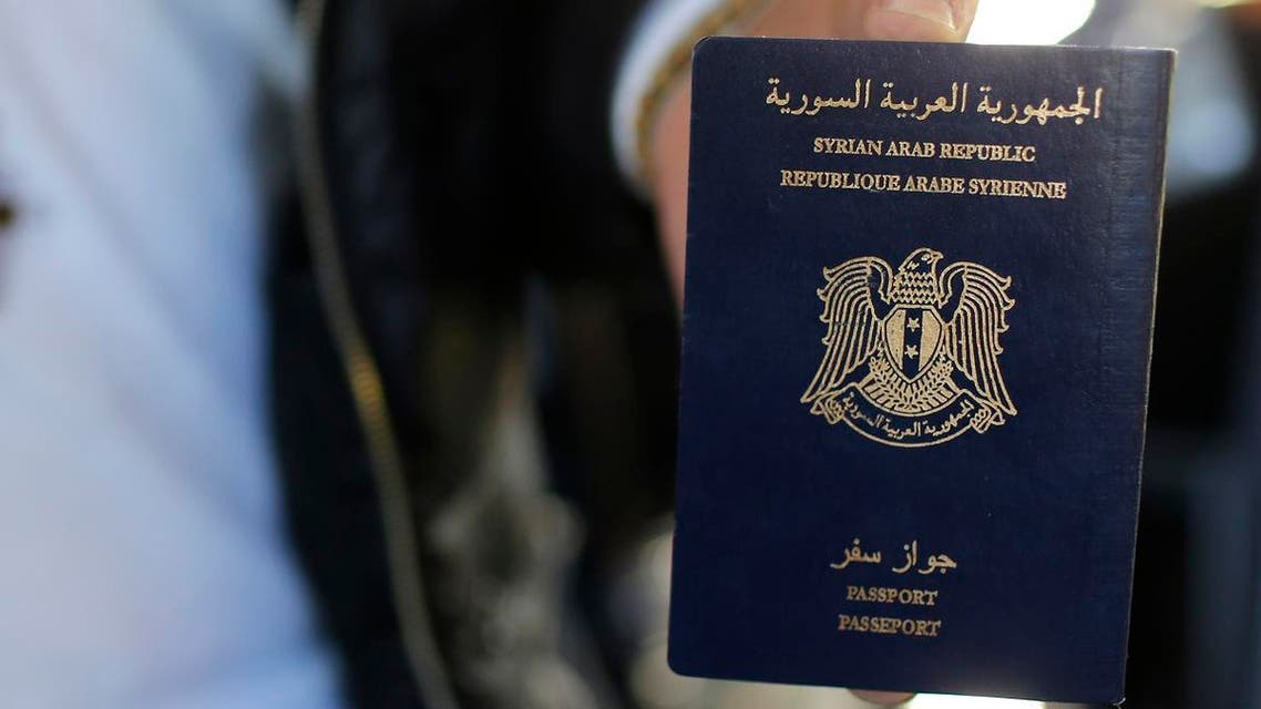Christian Syrian refugee Ghassan Aleid displays his Syrian passport at a terminal at the Charles-de-Gaulle Airport in Roissy, France, October 2, 2015. After the efforts of the mayor of Le Mans and a family member, a doctor residing in Le Mans, France accorded travel visas, requested a year ago, for the family who fled the conflict in Syria. REUTERS/Stephane Mahe