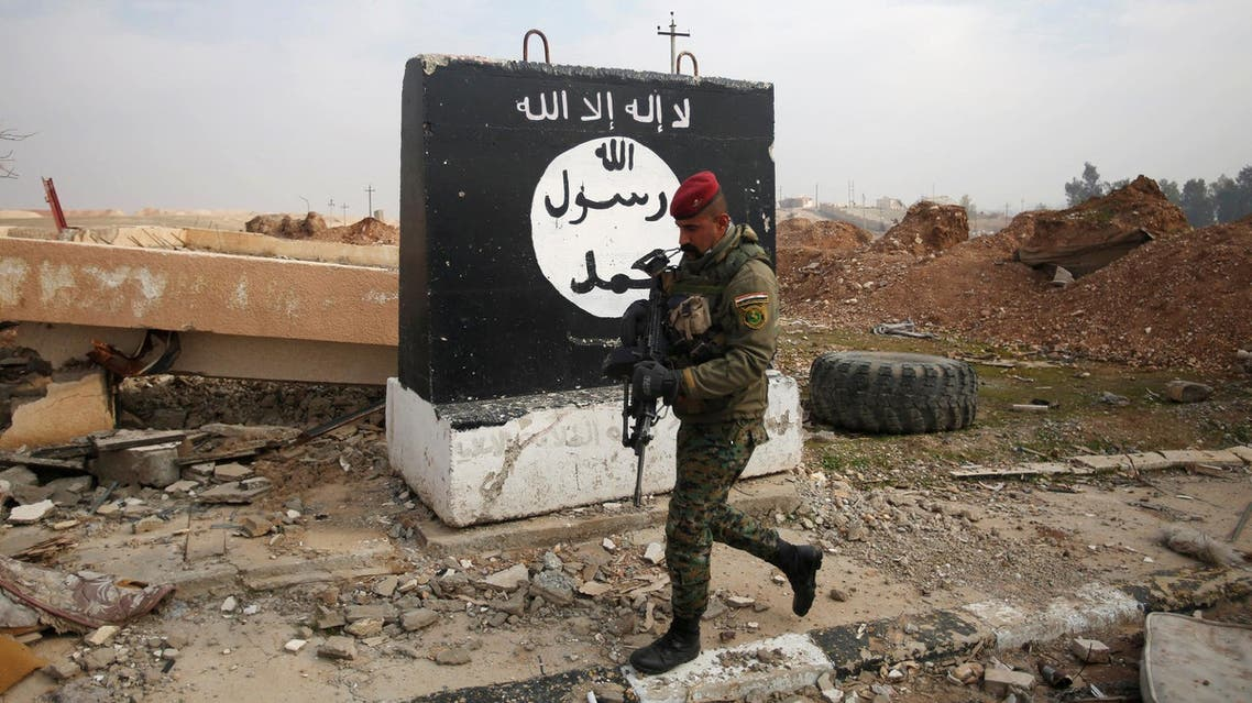 An Iraqi soldier walks next to a wall painted with the black flag commonly used by ISIS militants, during a battle with ISIS militants near Arabi neighborhood, north of Mosul, Iraq, January 21, 2017. (Reuters)