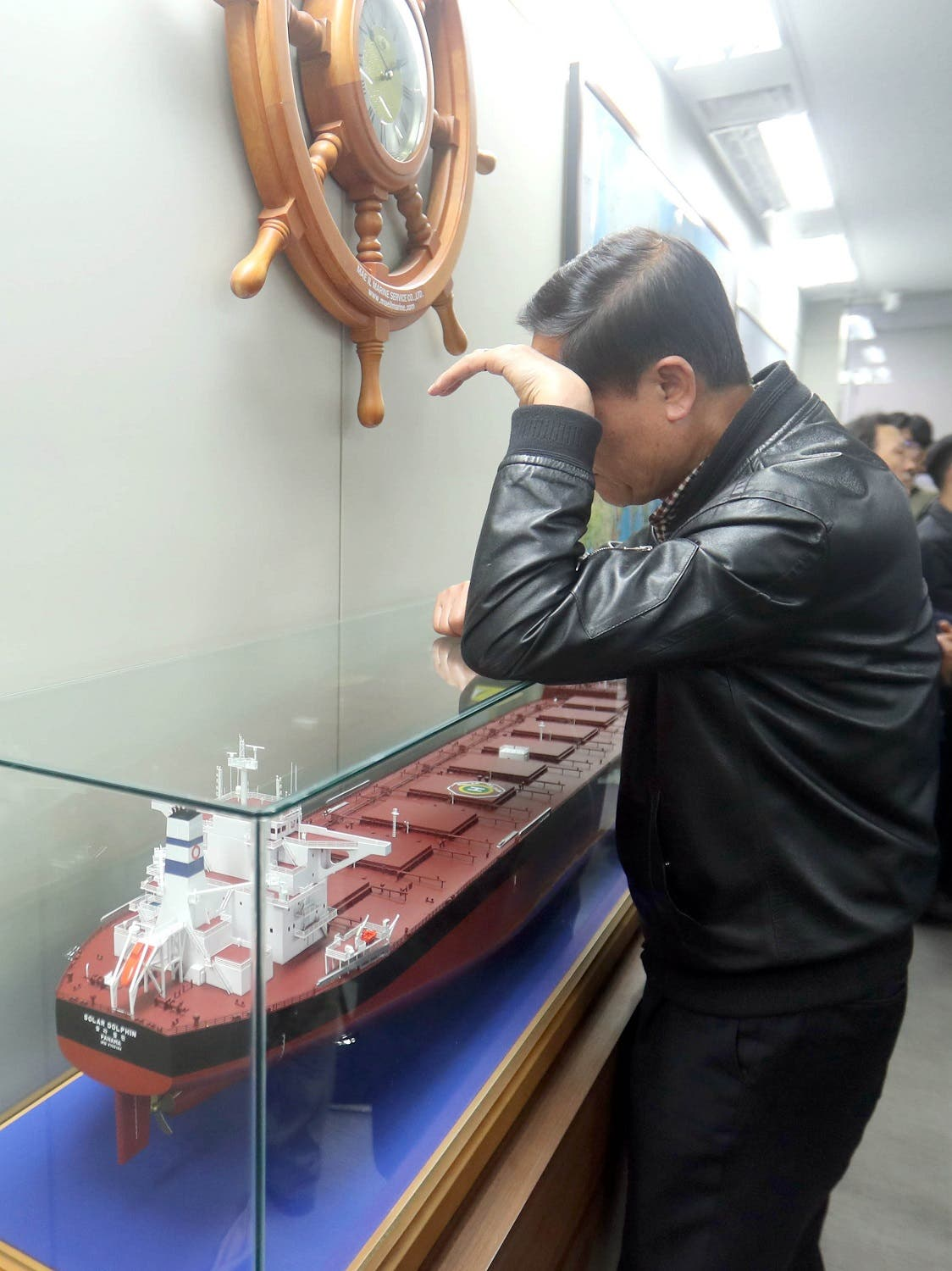 A relative of a missing crew member on board the Stella Daisy cargo ship waits for news beside a scale model display of a ship in the Polaris Shipping fleet, at one of the company's offices in the southern port city of Busan on April 2, 2017 (Photo: YONHAP/AFP)
