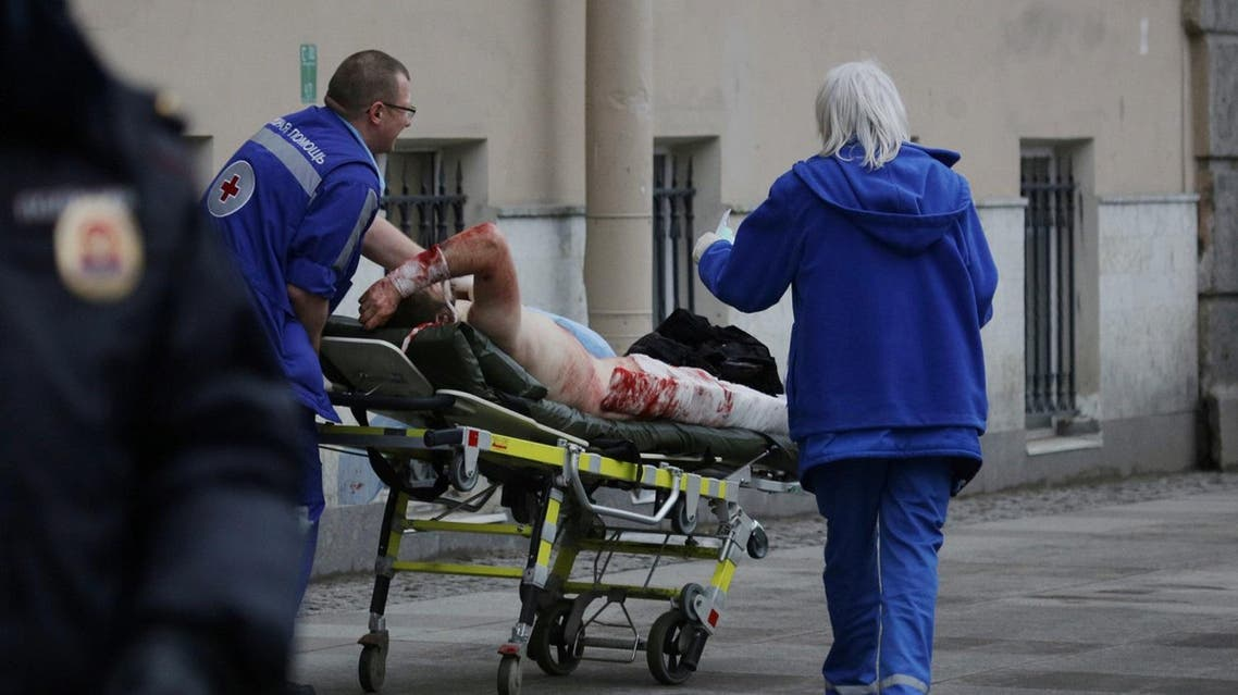 An injured person is helped by emergency services outside Sennaya Ploshchad metro station. (Reuters)