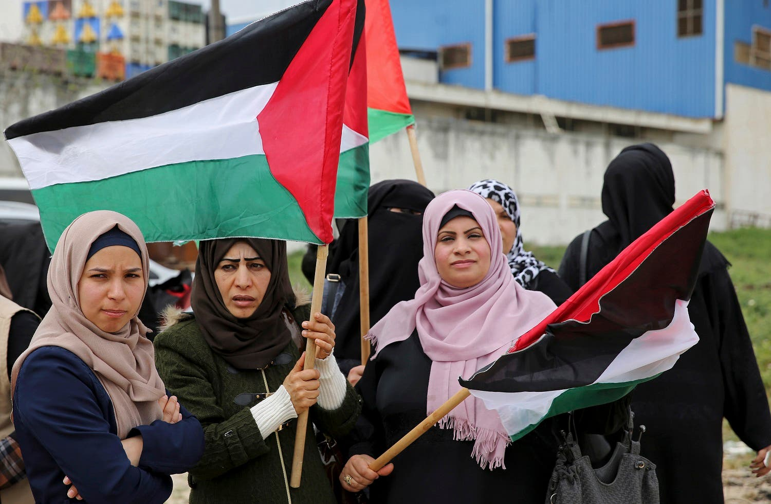 Women wave flags during a rally marking the 41st anniversary of Land Day, on the Palestinian side of the Beit Hanoun border crossing between Israel and the Gaza Strip on March 30, 2017. (AP)