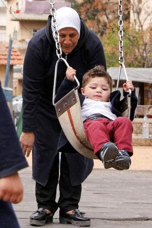 Hajar Saleh pushes her grandson Jaafar on a swing at a garden in the Damascus district of Mezzeh, Syria March 30, 2017. REUTERS/Omar Sanadiki