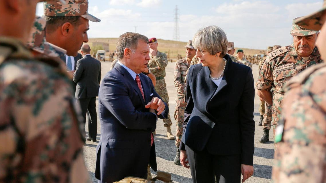 Jordan's King Abdullah II chats with British Prime Minister Theresa May as they visit a military base in Amman suburbs. (Reuters)