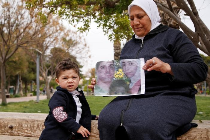 Hajar Saleh poses with her grandson Jaafar as she holds a picture depicting Jaafar's parents, Amina Saleh and her husband Imad Azouz who were killed fleeing Syria's civil war, at a garden in the Damascus district of Mezzeh, Syria March 30, 2017. REUTERS/Omar Sanadiki