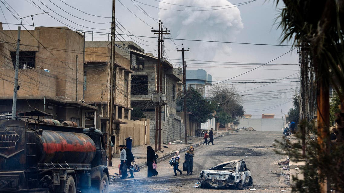 Iraqis walk down a street while smoke rises in the background following a car bomb explosion in eastern Mosul, on January 15, 2017, during an ongoing military operation by security forces against Islamic State (IS) group jihadists