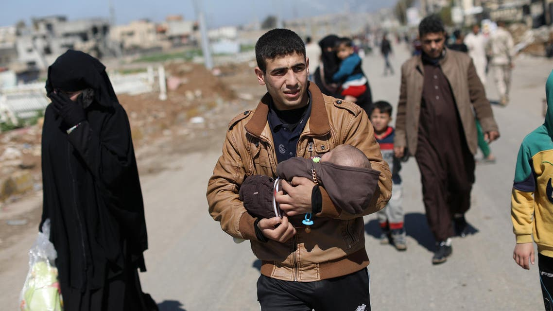 An Iraqi man carries a baby on his arms as he walks along a street after fleeing his neighborhood in Mosul, Iraq, April 4, 2017