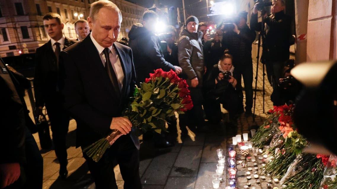 Russian president Vladimir Putin puts flowers down outside Tekhnologicheskiy Institut metro station in St. Petersburg, Russia, April 3, 2017. (AP)