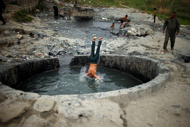 An Iraqi boy jumps into a sulfur pond at Hammam al-Alil city south of Mosul, Iraq April 3, 2017. Picture taken April 3, 2017 (Photo: Reuters/Suhaib Salem)