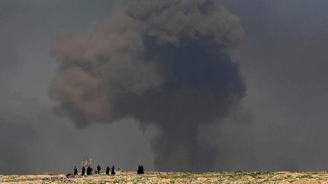 In this March 9, 2017 file photo, a large cloud of smoke rises during fighting between Iraqi security forces and ISIS militants as civilians walk toward Iraqi security. (AP) forces after fleeing their homes on the western side of Mosul, Iraq. (AP)