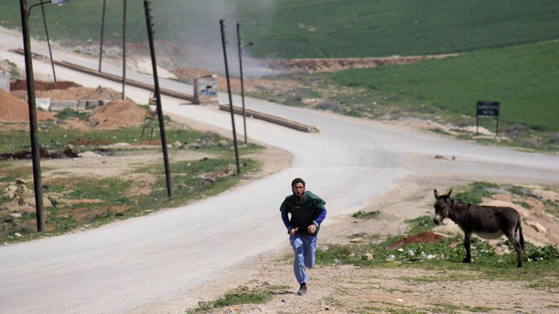 A Syrian medic runs for cover during the air strikes which hit a hospital in Khan Sheikhun on April 4, 2017. (AFP)
