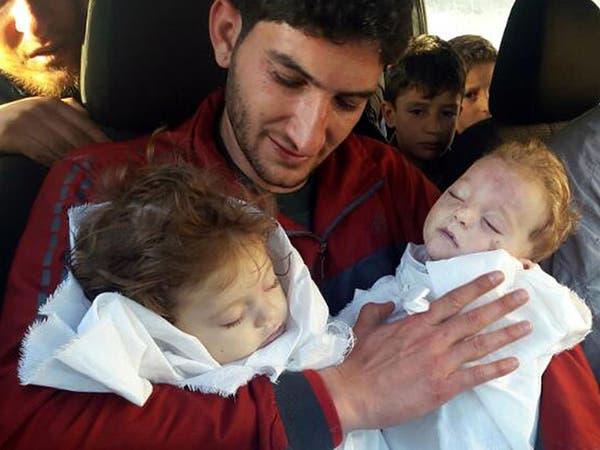 صور مؤلمة لوالد يحتضن جثماني توأمه بعد مجزرة إدلب