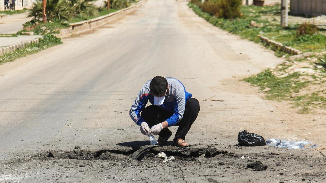 A Syrian man collects samples from the site of a suspected toxic gas attack in Khan Sheikhun, in Syria's Idlib province, on April 5, 2017. (AFP)