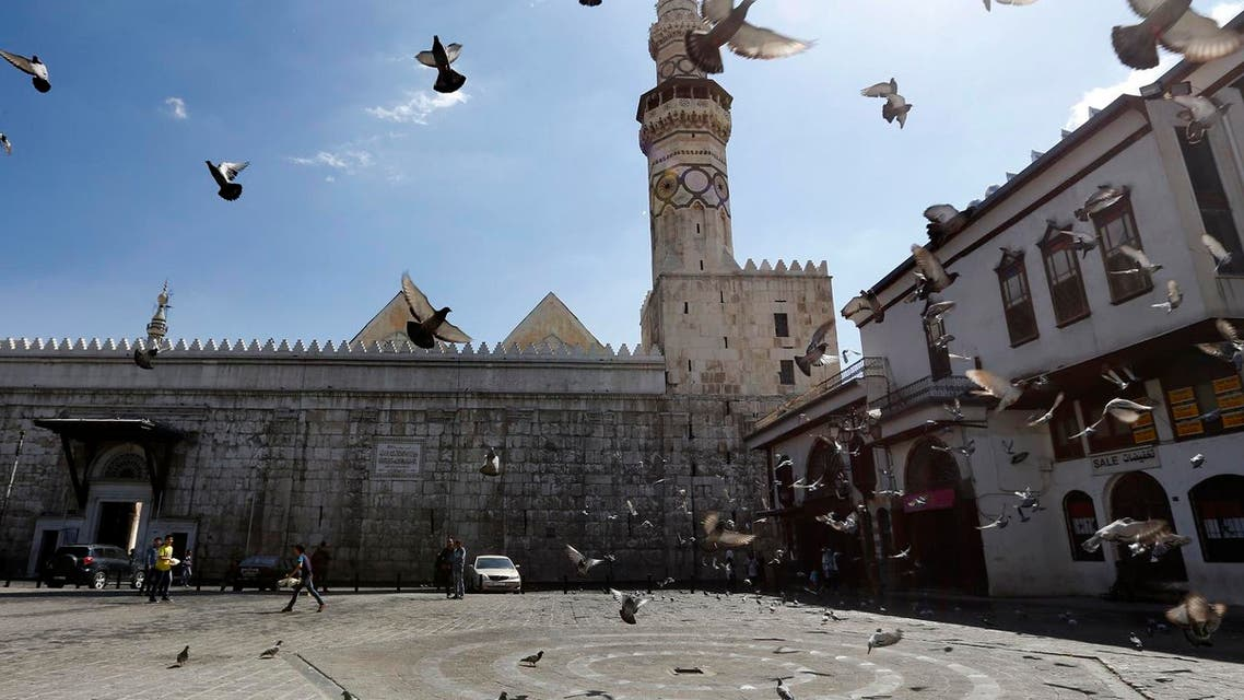 Pigeons fly in front of the Umayad Mosque, also known as the Grand Mosque of Damascus, on April 7, 2017. (AFP)