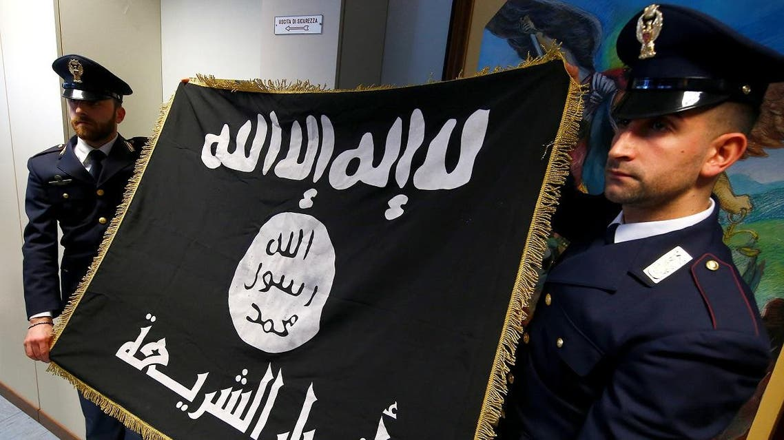Police officers hold a black Islamic State flag that was seized in a raid, at a news conference held at the police headquarters in Rome, Italy, January 10, 2017.