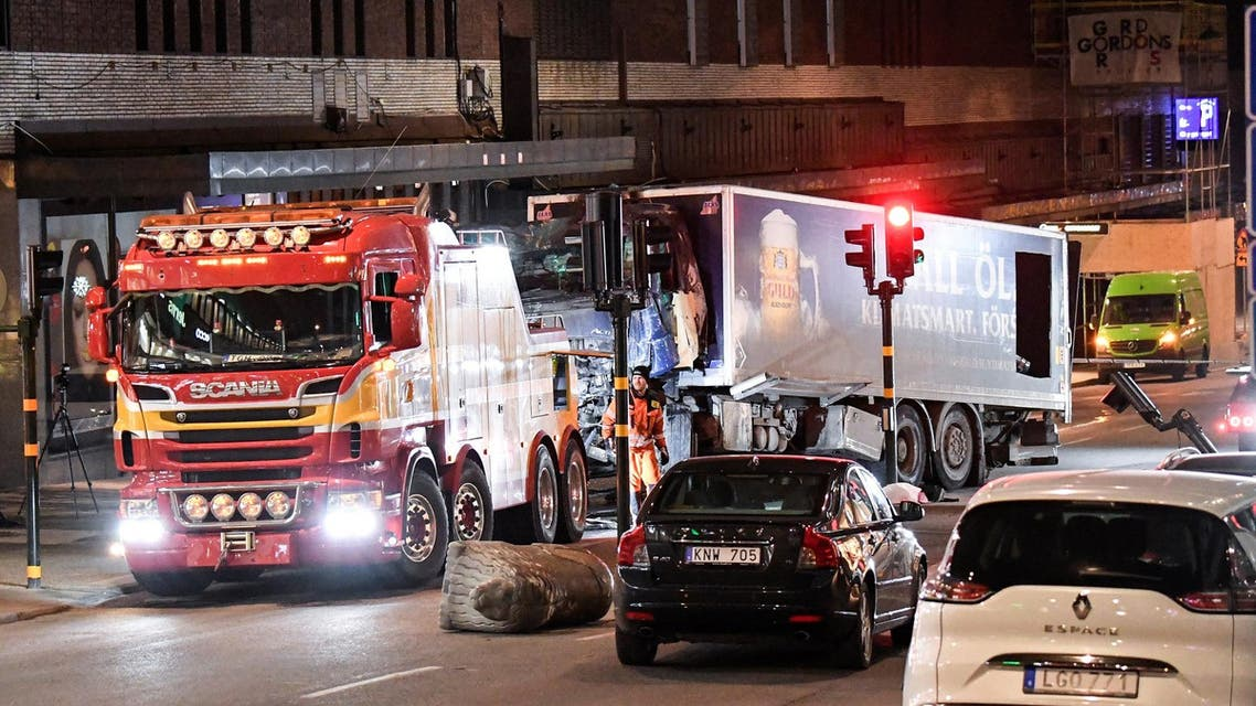 Tow trucks pull away the beer truck that crashed into the department store Ahlens after plowing down the Drottninggatan Street in central Stockholm, Sweden, April 8, 2017. (Reuters)