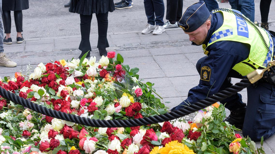A policeman lays flowers near the crime scene in central Stockholm on April 8, 2017, the day after a hijacked beer truck plowed into pedestrians and crashed into Ahlens department store. (Reuters)