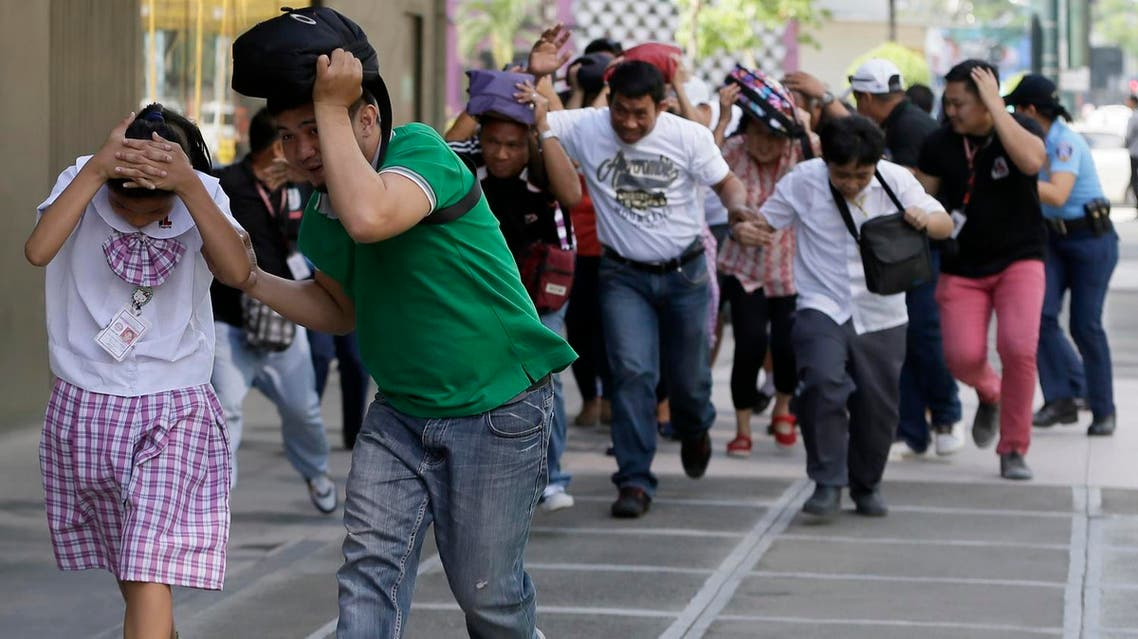 File photo of people rushing to safety to simulate a powerful earthquake during a drill  Taguig city east of Manila. (AP)