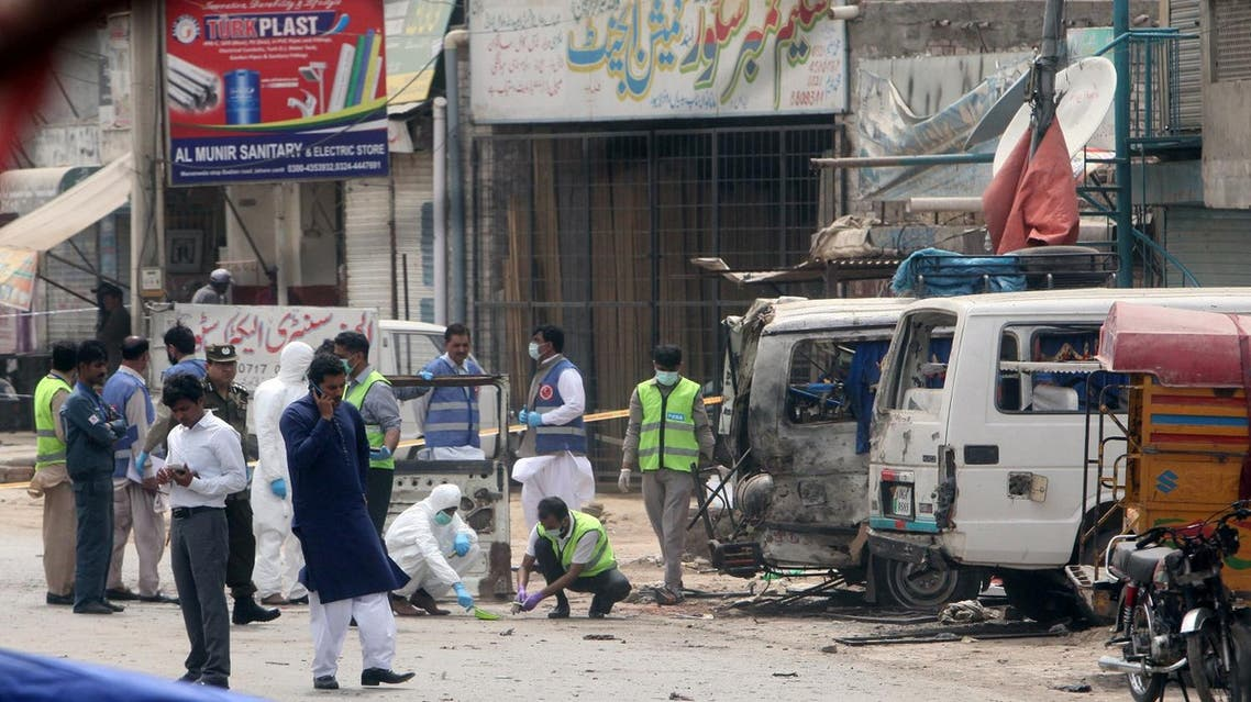 Forensic experts search for evidence at the site of an explosion, near vehicles taking part in census, in Lahore, Pakistan, April 5, 2017. REUTERS