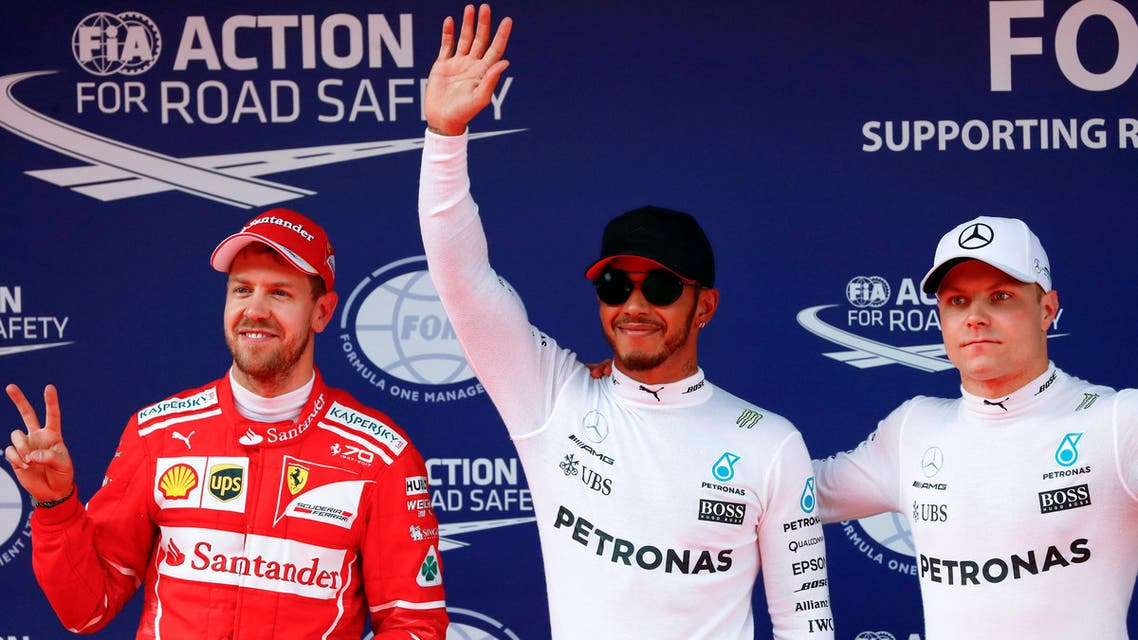 Mercedes driver Lewis Hamilton (center) of Britain reacts after setting pole position in qualifying alongside team mate Valtteri Bottas (right) of Finland and Ferrari's Sebastian Vettel of Germany at the Shanghai International Circuit. (Reuters)
