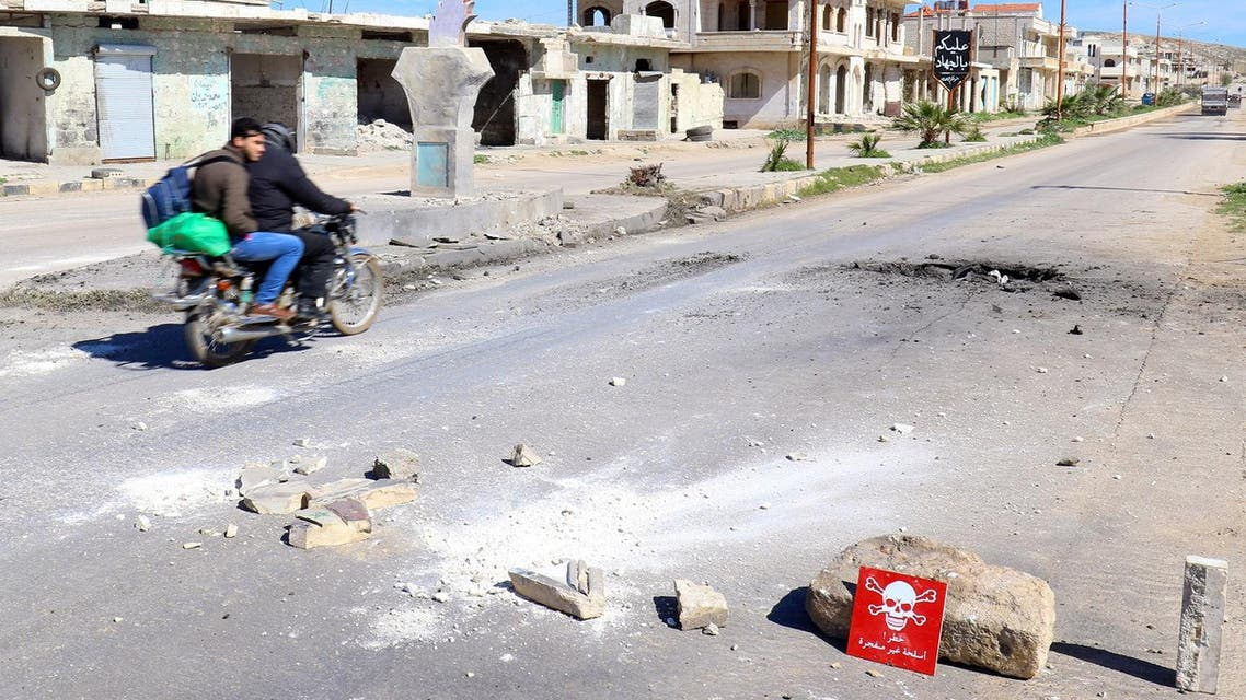 """Men ride a motorbike past a hazard sign at a site hit by an airstrike on Tuesday in the town of Khan Sheikhoun in rebel-held Idlib, Syria April 5, 2017. The hazard sign reads, """"Danger, unexploded ammunition"""" (File Photo: Reuters/Ammar Abdullah)"""