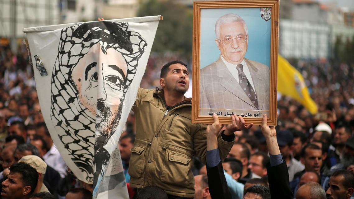 A Palestinian Authority employee holds a painted poster depicting late Yasser Arafat and a poster of President Mahmoud Abbas during a protest against deductions on their salaries, in Gaza City on April 8, 2017. (Reuters)