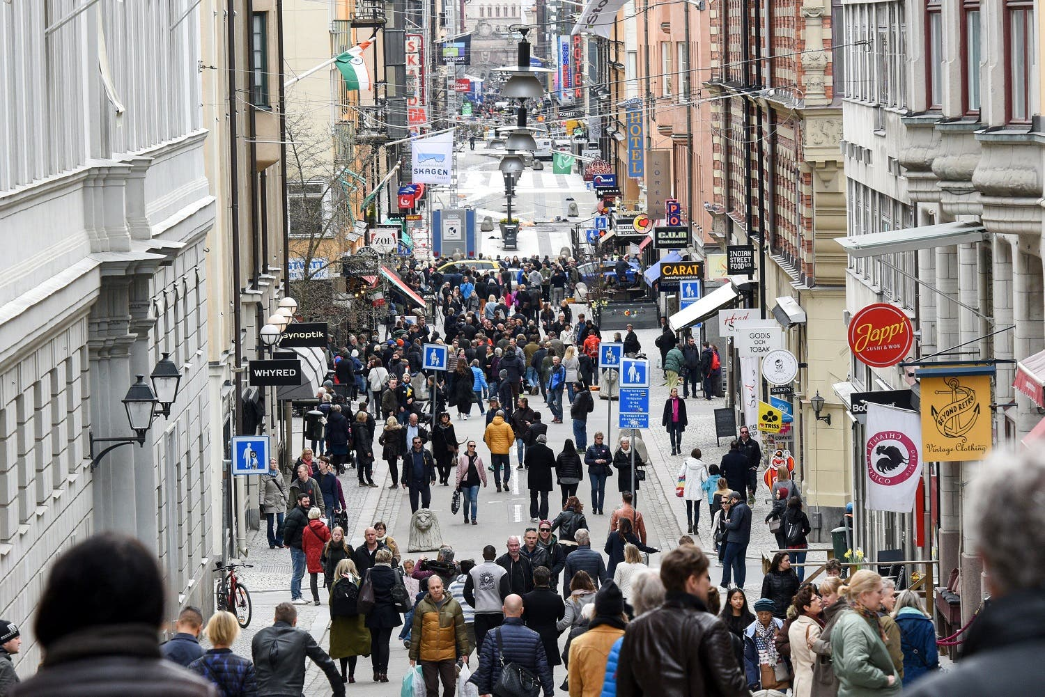 People gather near the crime scene in central Stockholm April 8, 2017, the day after a hijacked beer truck plowed into pedestrians on Drottninggatan and crashed into Ahlens department store. (Reuters)