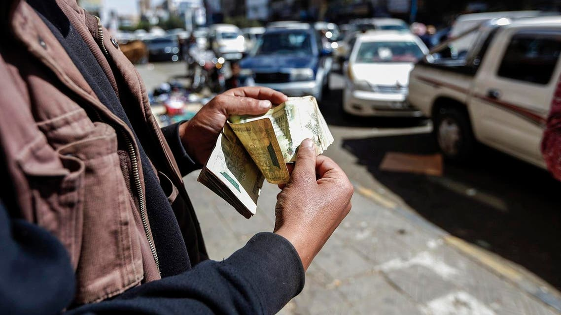 A Yemeni man counts stacks of Yemeni rials on a street in the capital Sanaa, on February 12, 2017. (AFP)