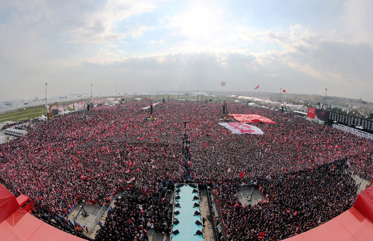 This handout picture taken and released on April 8, 2017 by the Turkish Presidential Press Service shows supporters waving the Turkish national flag and 'YES' banners as Turkish President Recep Tayyip Erdogan delivers a speech during a campaign rally for the 'yes' vote in a constitutional referendum at the Yenikapi Square in Istanbul. (AFP)