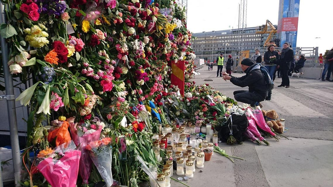 A man takes a picture of flowers on the fence by Ahlens department store following Friday's attack in central Stockholm, Sweden, April 9, 2017. ( Reuters)