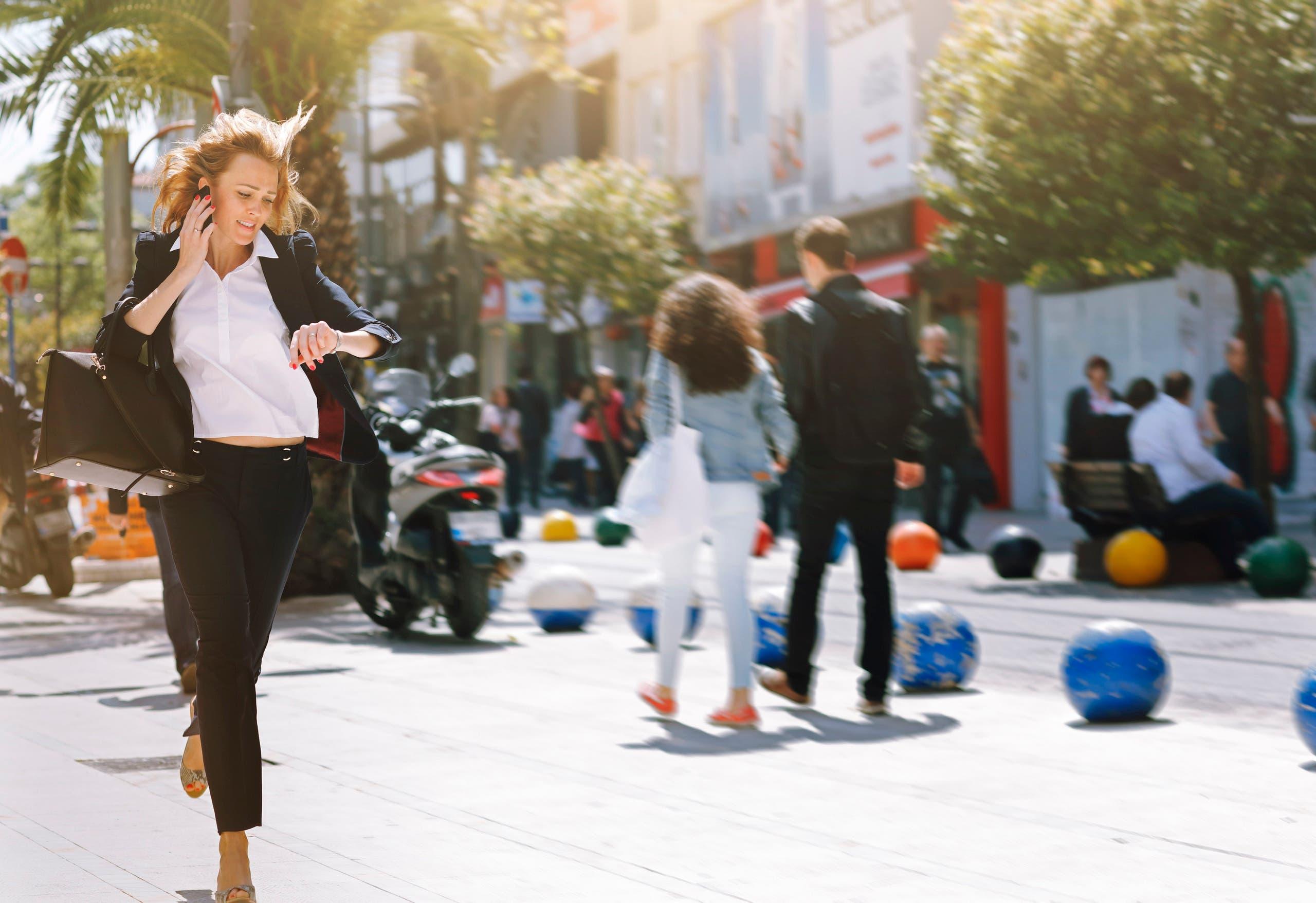 Business woman rushing to work running late. (Stock image)