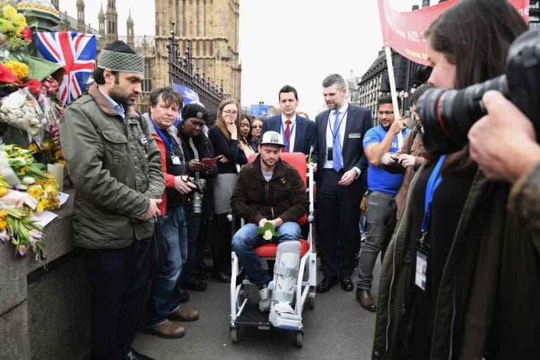 صديق الضحية مصاباً بكسر في ساقه وعلى كرسي متحرك أثناء مراسم تشييع صديقته