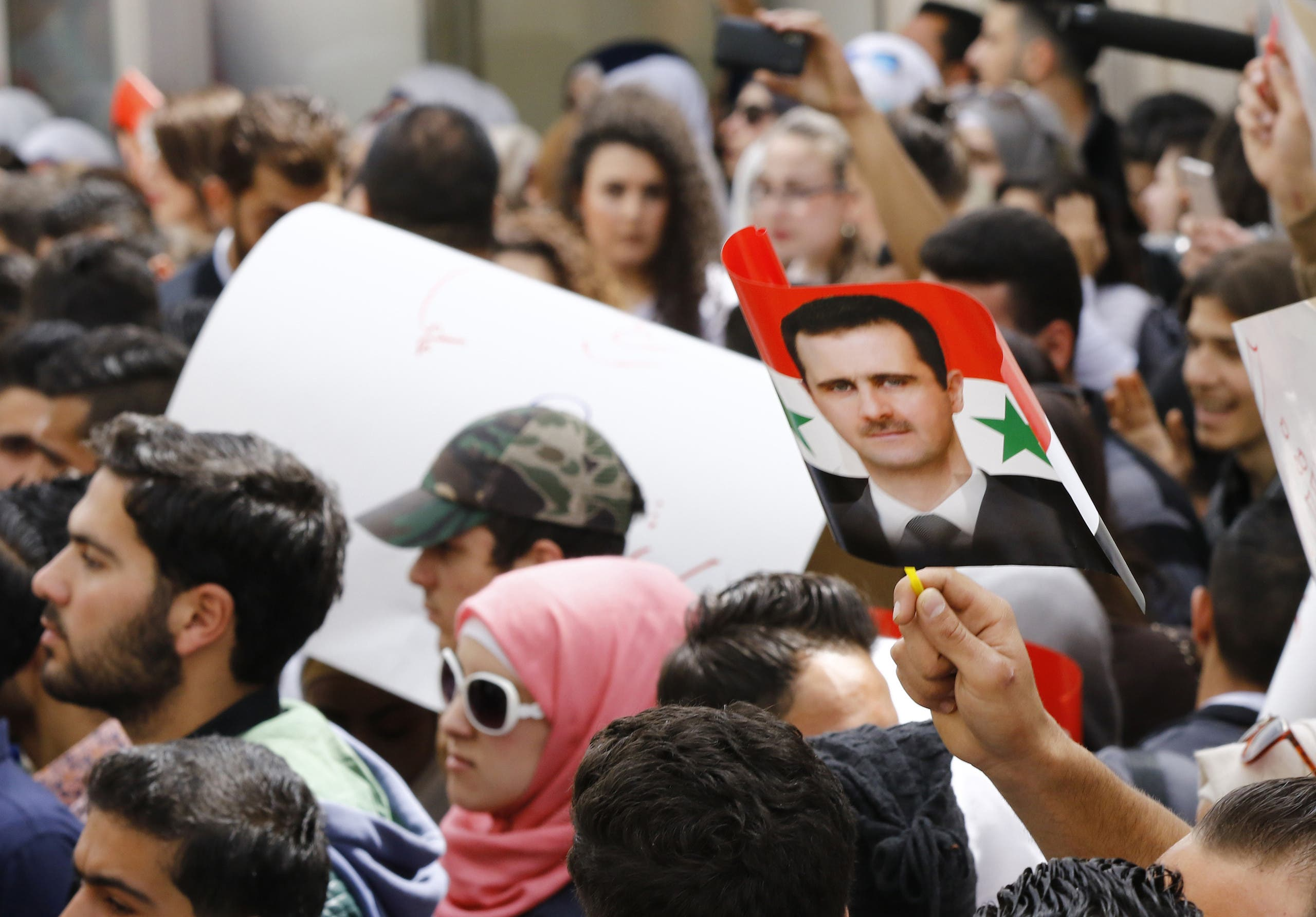 Syrian protestors wave a flag bearing a portrait of their country's President Bashar al-Assad during a demonstration in his support outside the United Nation's (UN) office in the capital Damascus, on April 11, 2017. AFP