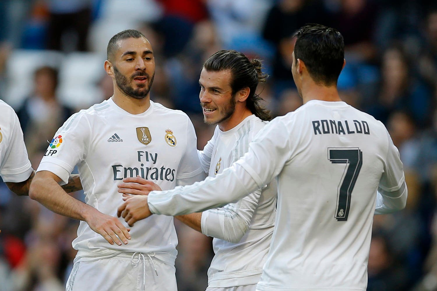 Real Madrid's Karim Benzema, left, celebrates with teammates Cristiano Ronaldo, right, and Gareth Bale after scoring their side's third goal against Getafe during the Spanish La Liga soccer match between Real Madrid and Getafe at the Santiago Bernabeu stadium in Madrid, Saturday, Dec. 5, 2015. Benzema scored twice and Ronaldo and Bale scored once each in Real Madrid's 4-1 victory. (AP)