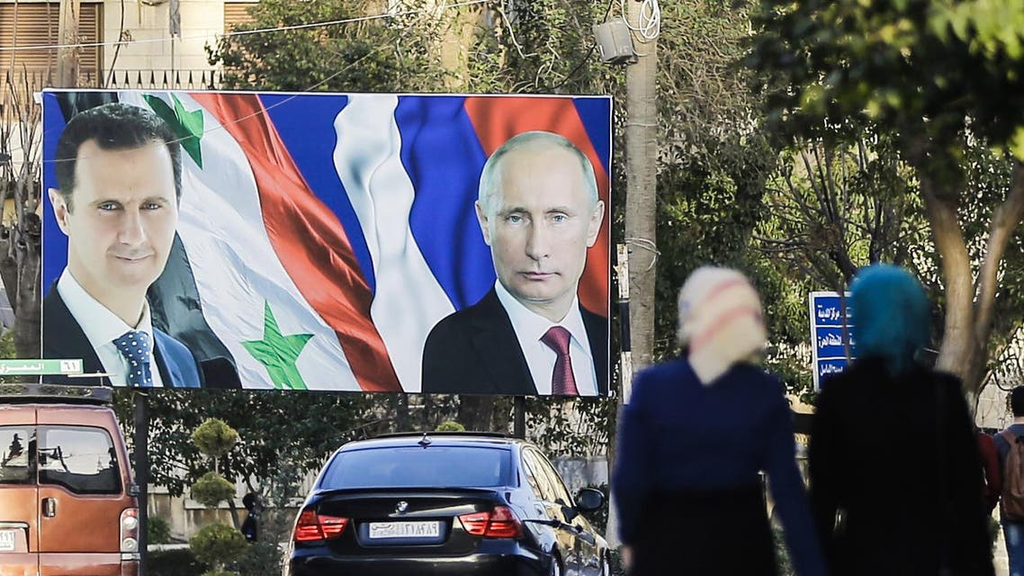 A picture taken on March 9, 2017 in the northern Syrian city of Aleppo, which was recaptured by government forces in December 2016, shows Syrians walking past a giant poster of Syrian President Bashar al-Assad (L) and his Russian counterpart Vladimir Putin (R). JOSEPH EID / AFP