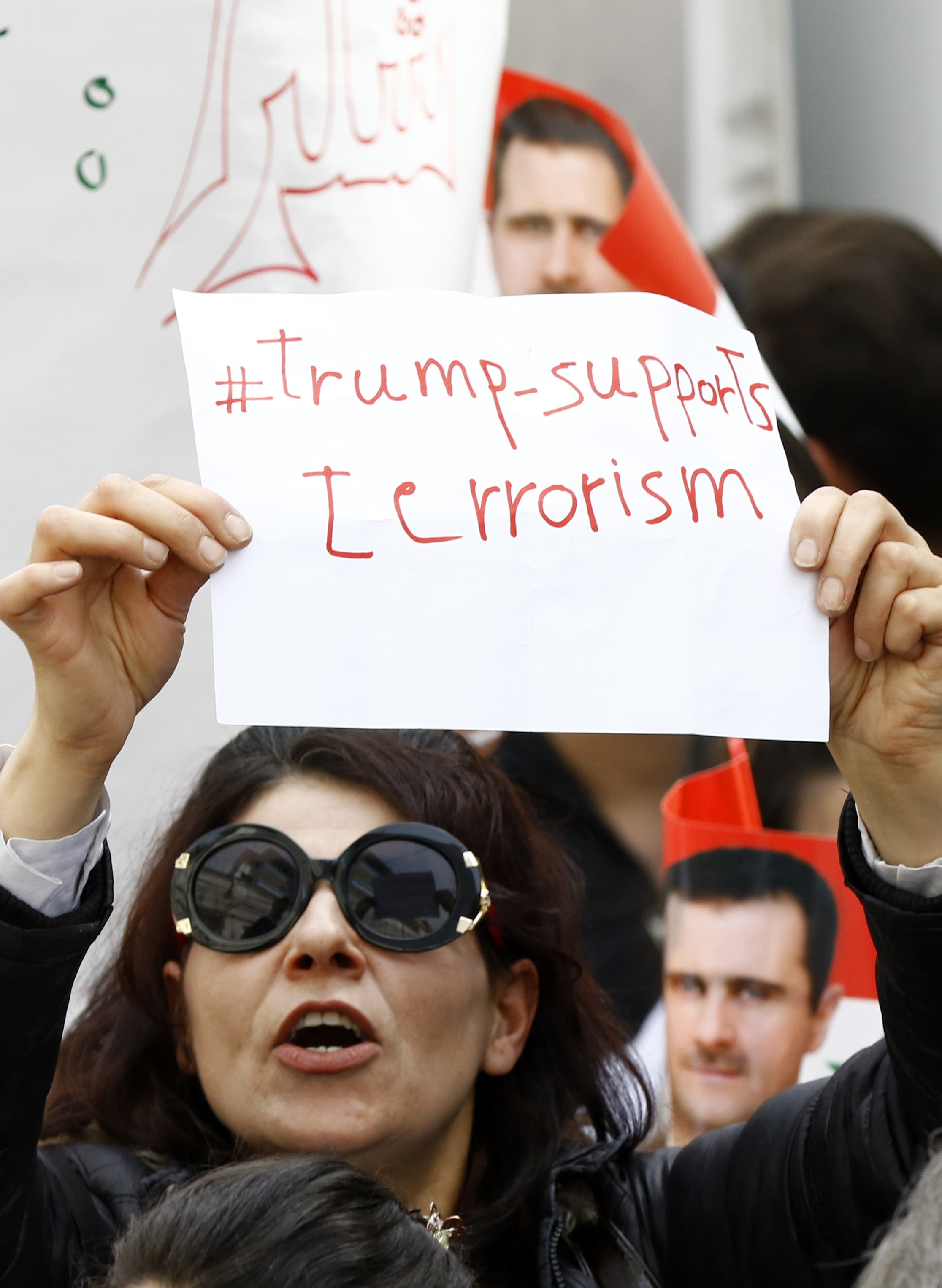 A Syrian protestor holds a placard during a demonstration outside the United Nation's (UN) office in the capital Damascus, on April 11, 2017, in support of their country's President Bashar al-Assad. afp