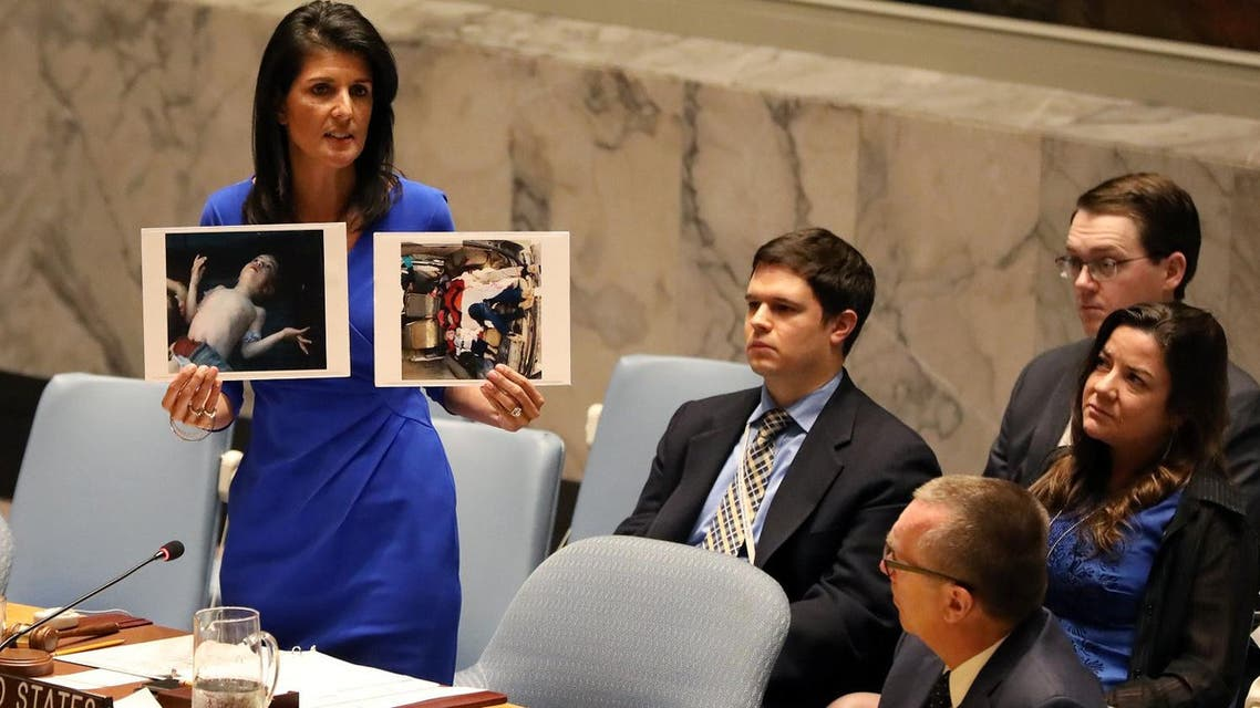 US Ambassador to the UN Nikki Haley holds photographs of victims during a meeting at the Security Council on Syria in New York on April 5, 2017. (Reuters)