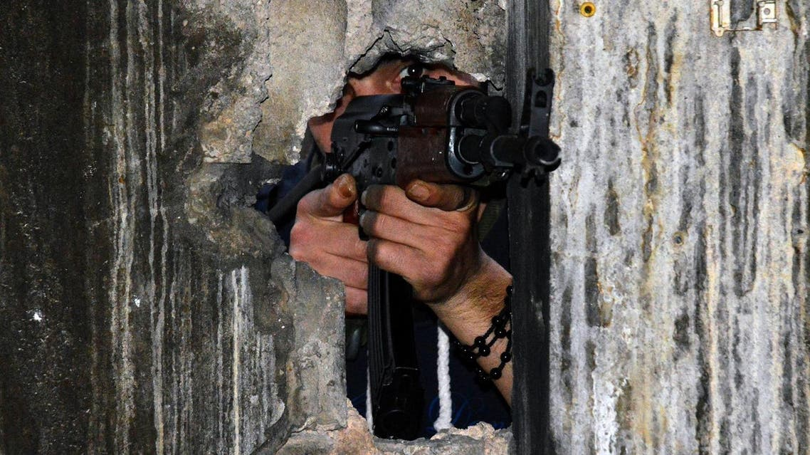 A member of the joint Palestinian security takes position through a hole in a wall with a kalashnikov assault rifle in Ain al-Hilweh camp, Lebanon's largest Palestinian refugee camp, near the southern coastal city of Sidon, on April 12, 2017, after clashes that took place earlier in the week between an extremist group and the security force. Fighting erupted on April 7, 2017 after Palestinian factions deployed throughout the camp as part of a joint security force aimed at combatting the influence of a local Islamic extremist group. (AFP)
