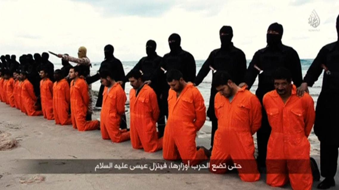 Men in orange jumpsuits purported to be Egyptian Christians held captive by the Islamic State (IS) kneel in front of armed men along a beach said to be near Tripoli, in this still image from an undated video made available on social media on February 15, 2015. reuters