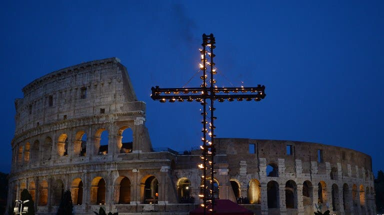 A cross is illuminated at the Colosseum prior the Via Crucis (Way of the Cross) torchlight procession on Good Friday, on April 14, 2017 in Rome. (AFP)