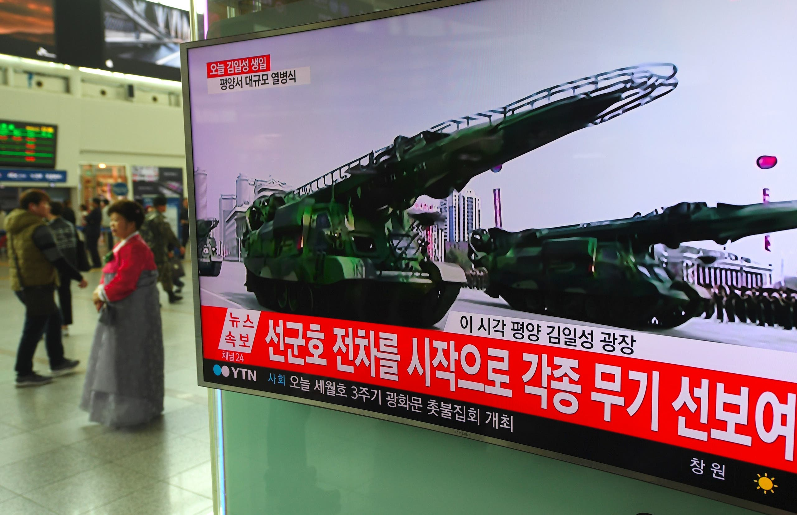 People watch a television news broadcasting live footage of a parade to mark the 105th anniversary of the birth of North Korea's founder Kim Il-Sung, at a railway station in Seoul on April 15, 2017.