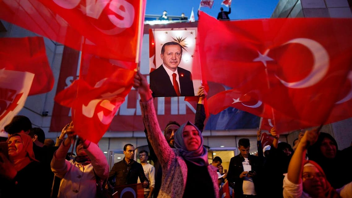 Supporters of Justice and Development party (AK) wave Turkish flags and hold a poster of Turkish President Recep Tayyip Erdogan outside its offices in Istanbul, Sunday, April 16, 2017. (AP)