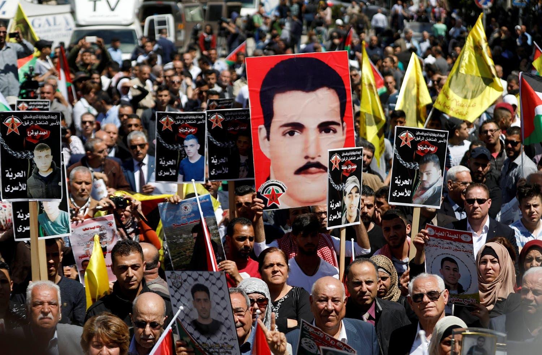 مغربی کنارے کے شہر رام اللہ میں سیکڑوں فلسطینی اسرائیلی جیلوں میں قید اپنے پیاروں کی تصاویر اٹھائے ریلی میں شریک ہیں۔