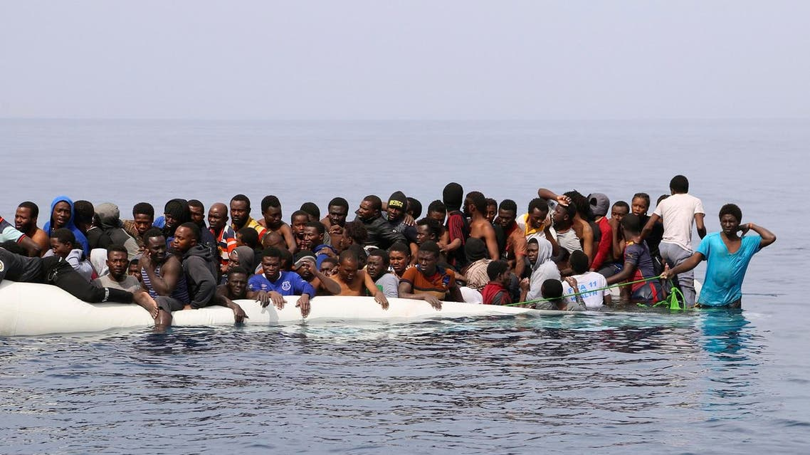 Migrants wait to be rescued from a sinking dingey off the Libyan coasal town of Zawiyah, east of the capital, on March 20, 2017, as they attempted to cross from the Mediterranean to Europe. (AFP)