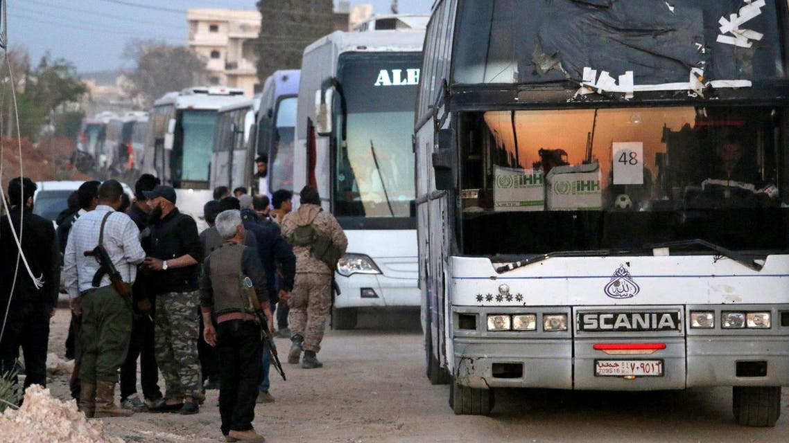 Syrian rebel fighters stand guard as buses bringing a new batch of evacuees from Waer, the last opposition-held district of Syria's third city Homs, arrive in the city of al-Bab in the northern Aleppo province at sunset on April 18, 2017. (AFP)