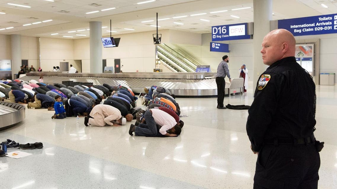 People pray in baggage claim area during a protest against the travel ban at Dallas/Fort Worth International Airport in Dallas, Texas on January 29, 2017. (Reuters)