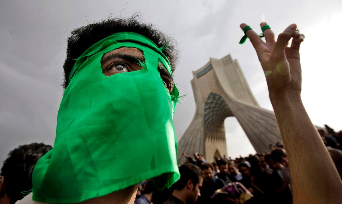 A demonstrator wears a mask in the party's color of green, due to fears of being identified, as hundreds of thousands of supporters of leading opposition presidential candidate Mir Hossein Mousavi turned out to protest the result of the 2009 election at a mass rally in Azadi (Freedom) square in Tehran, Iran. (File photo: AP)