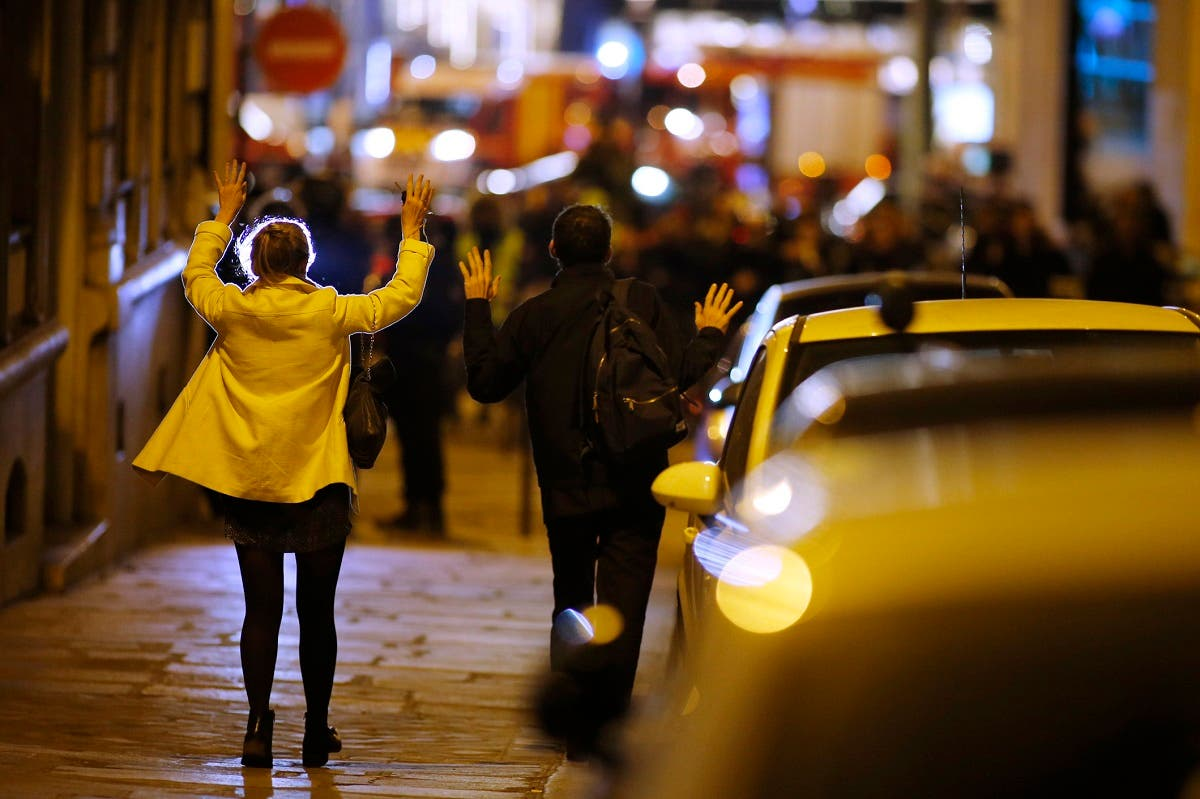 People raise their arms to show their hands as they walk towards police on a side road near the Champs Elysees Avenue after two policemen were killed and another wounded in a shooting incident in Paris. (Reuters)